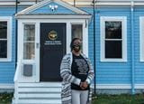 Monica Cannon-Grant standing in front of the doorway to her organization, Violence in Boston. The organization's logo is on the black door, and the building has blue siding. Monica is wearing a black t-shirt with white writing on the front, and a black and white cardigan and gray pants. She's wearing a black face mask with the Violence in Boston logo on it.