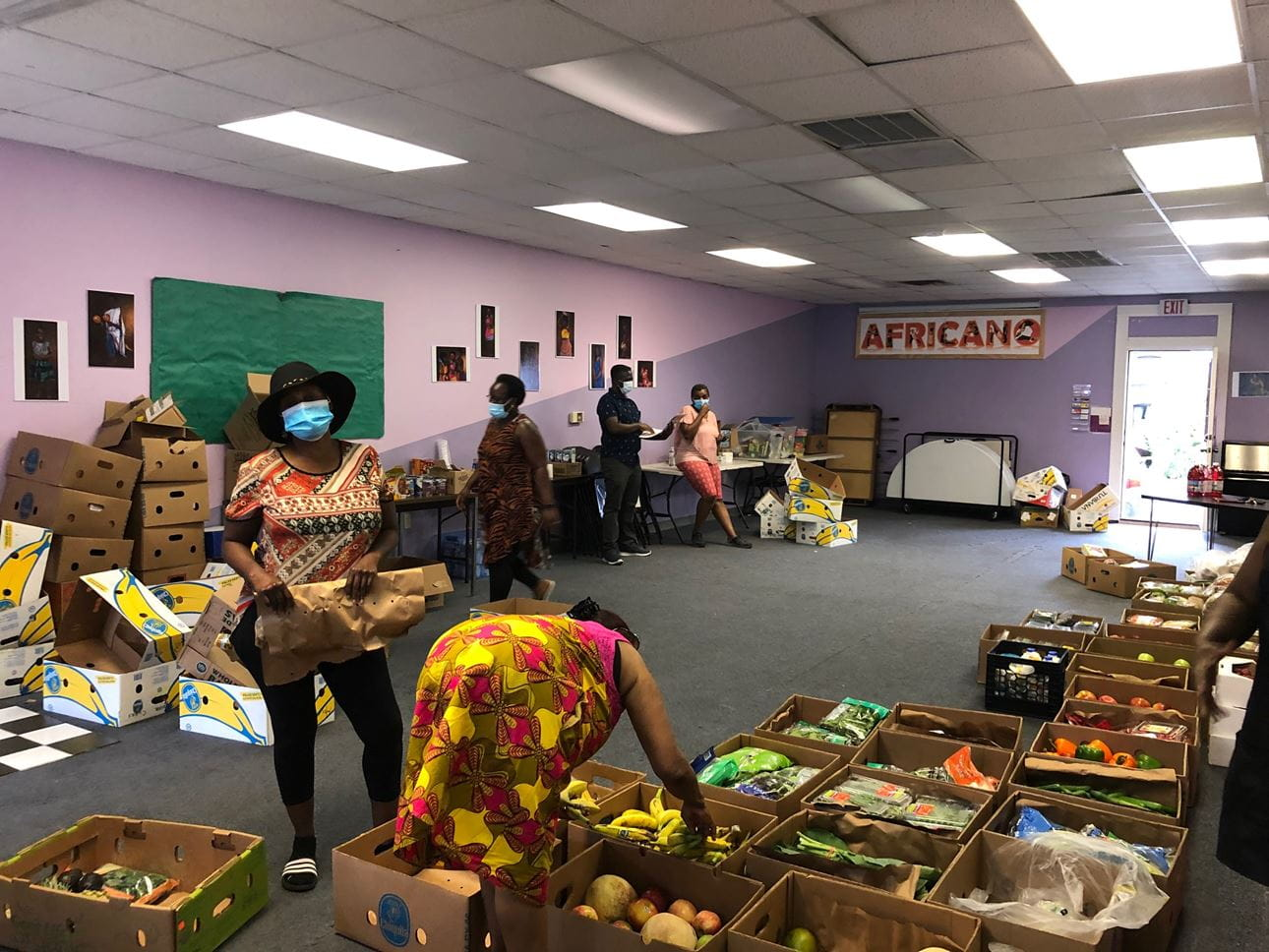 Women at Africano Waltham standing among boxes full of produce for a food drive.