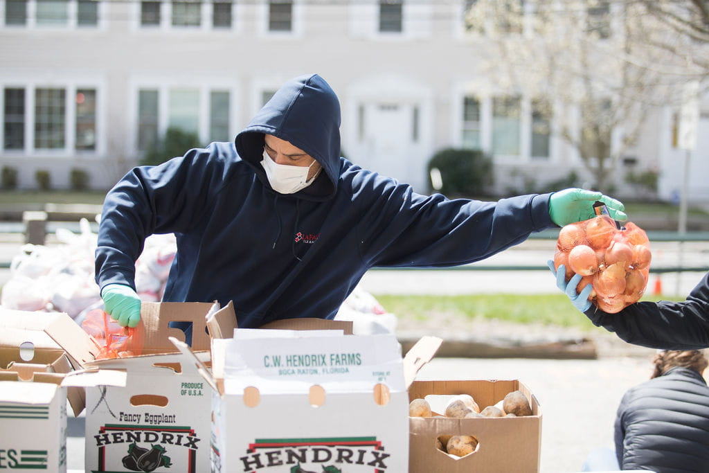 A man wearing a black hoodie and protective mask is taking produce out of boxes and handing it to someone on his left.