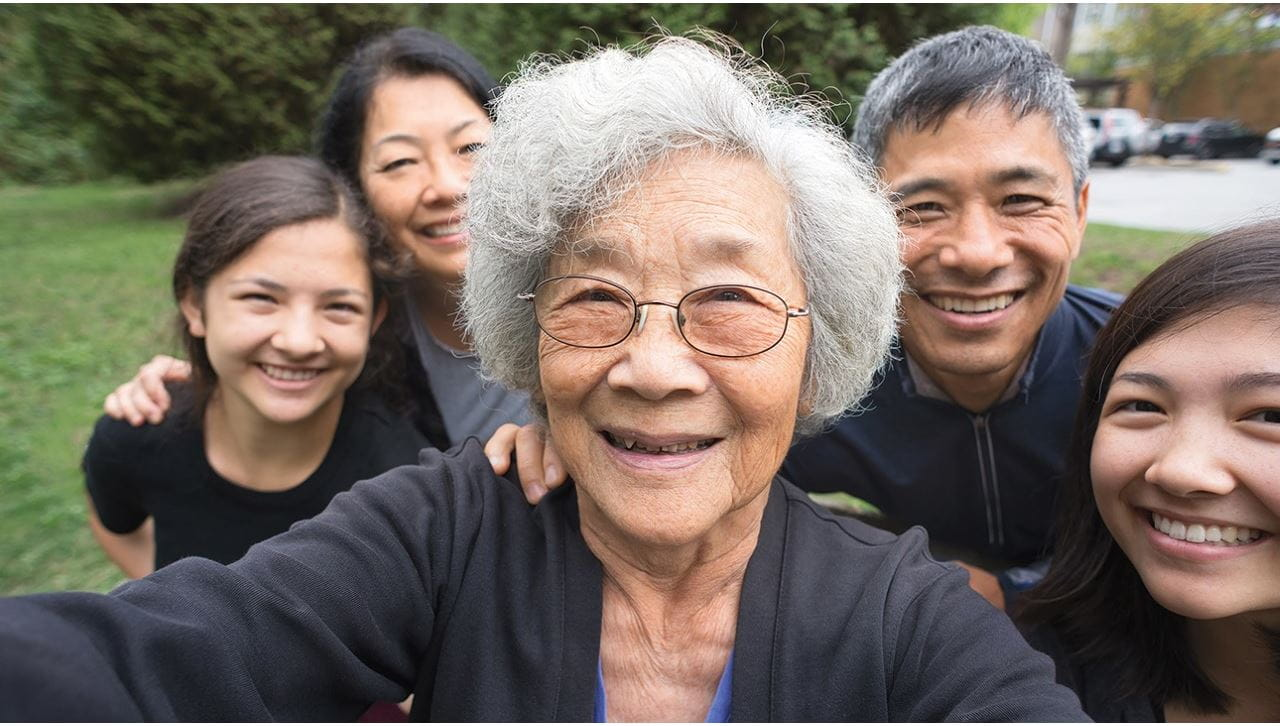 A selfie of an Asian family. An elderly woman in the center is taking the selfie. Behind her from left to right are a young girl, a woman, a man and another young girl. They are outside; green grass and trees are behind them. They're smiling and wearing black or navy blue shirts.