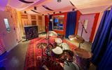 Studio B at The Record Co. - a warmly lit recording studio with a red carpet and a drum set in the center of the room. Photo by Jenny Bergman.