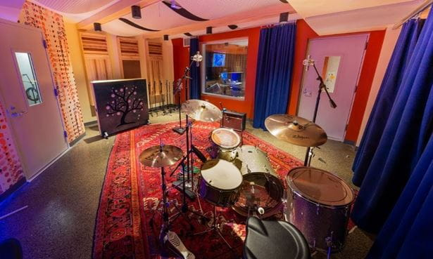 Studio B at The Record Co. - a warmly lit recording studio with a red carpet and a drum set in the center of the room.