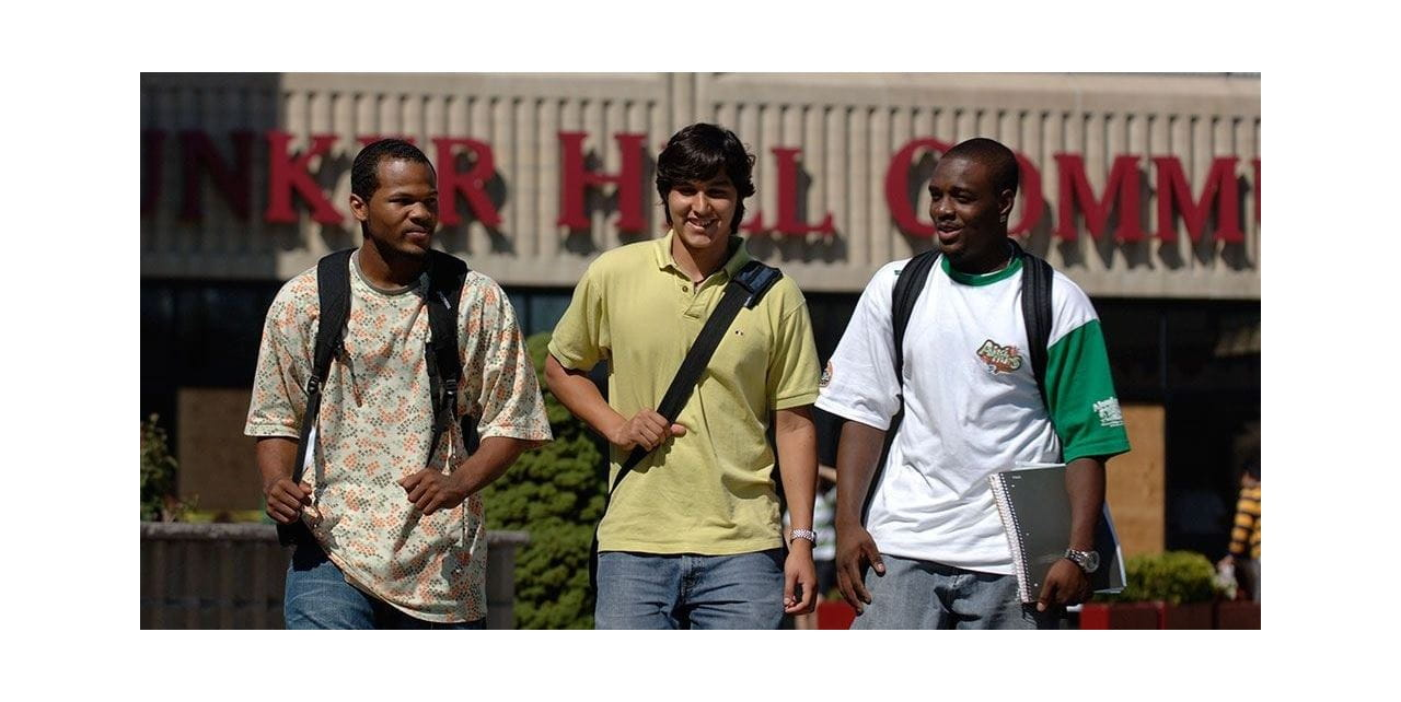 3 male students walking next to each other, smiling, with part of the main red Bunker Hill Community College sign on one of its buildings in the background.