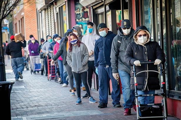 A large number of people standing in line outside - all wearing masks - at a food bank.