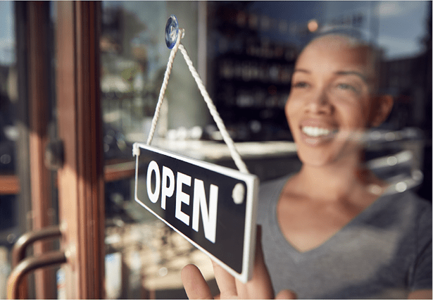 "A woman of color standing behind a glass door, smiling as she hangs up an ""open"" sign."