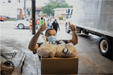 A man standing behind a stack of boxes and bags of food, wearing a mask and holding two thumbs up. A truck and other food bank volunteers in the background.
