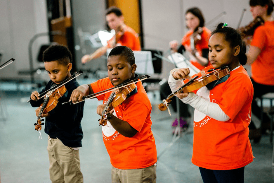 3 young children playing violins in a room with other youth behind them playing violins. They're all wearing orange t shirts.