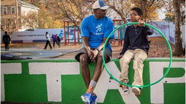 Playworks coach and student talk on playground