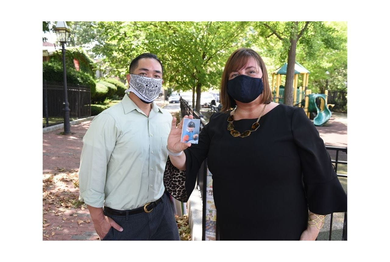 Cliff Kwong and Amy O'Leary standing next to each other wearing masks. Amy is holding up a photo of a young boy in a baseball uniform. A brick sidewalk trails behind them, with green trees in the background. It's a sunny day.