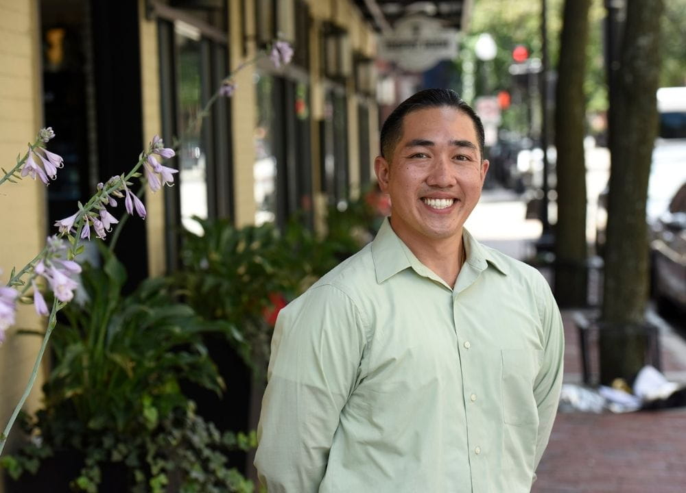 Cliff Kwong standing with his arms behind their back, smiling. He's wearing a long-sleeved, collared, light green shirt. He's standing on a brick sidewalks that trails behind him, along with a yellow building with storefronts and green shrubs on the left. Small purple flowers are peaking into the left side of the image.