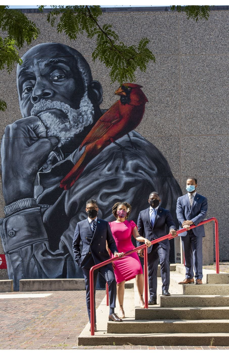 Imari Paris Jeffries, Sheena Collier, Willie Brodick and Segun Idowu standing in a row on a set of concrete stairs, outside with masks on. Behind them is a concrete wall witha. large mural of Mel King with a cardinal on his shoulder. Branches and leaves of a tree peak into the top of the frame.
