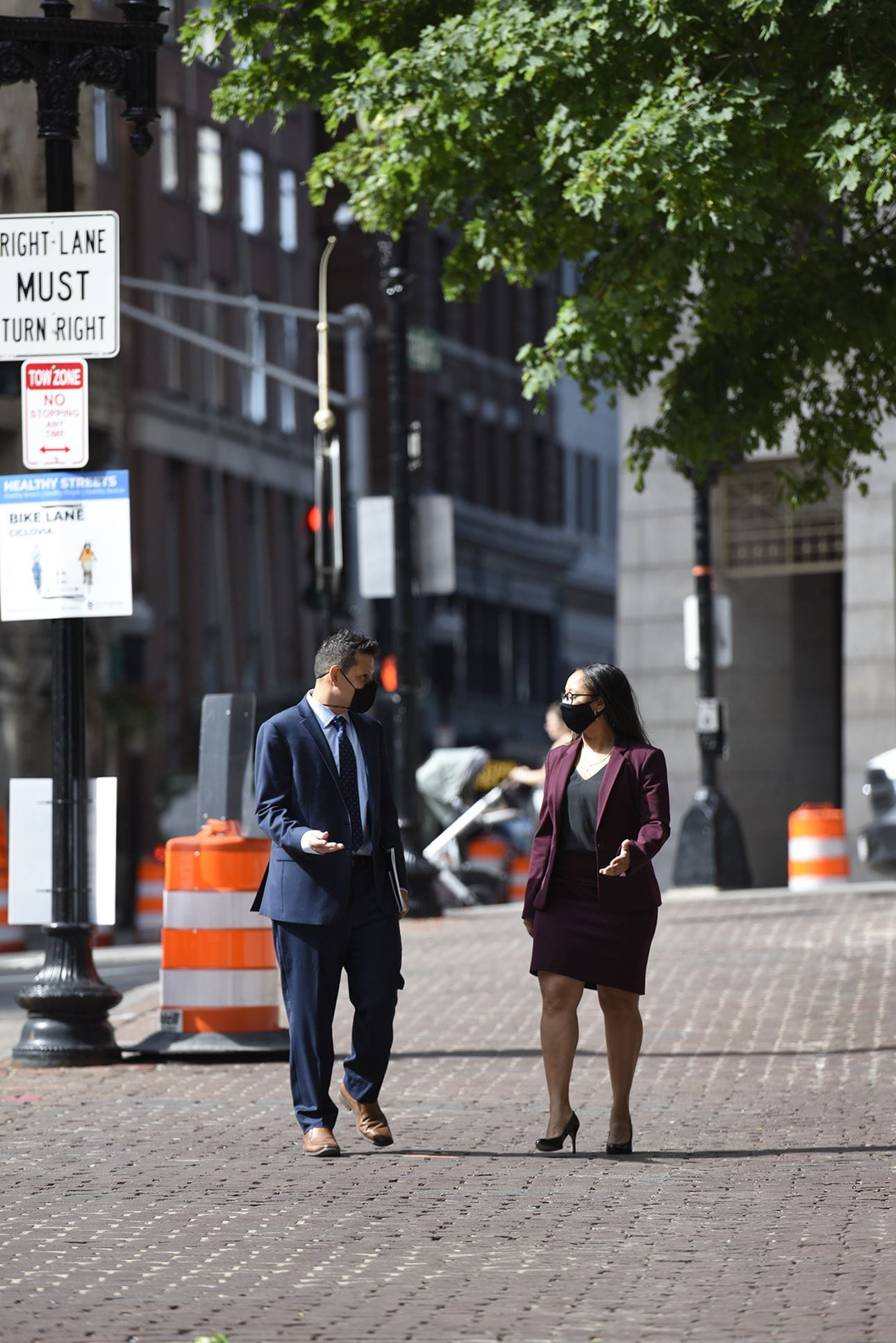 Ivan Espinoza Madrigal and Sophia Hall walking next to each other on a brick sidewalk in the city. They are both wearing masks. He's wearing a dark blue suit and she's wearing a dark purple suit jacket and skirt. They're walking towards the camera and facing each other, gesturing as if having a conversation.