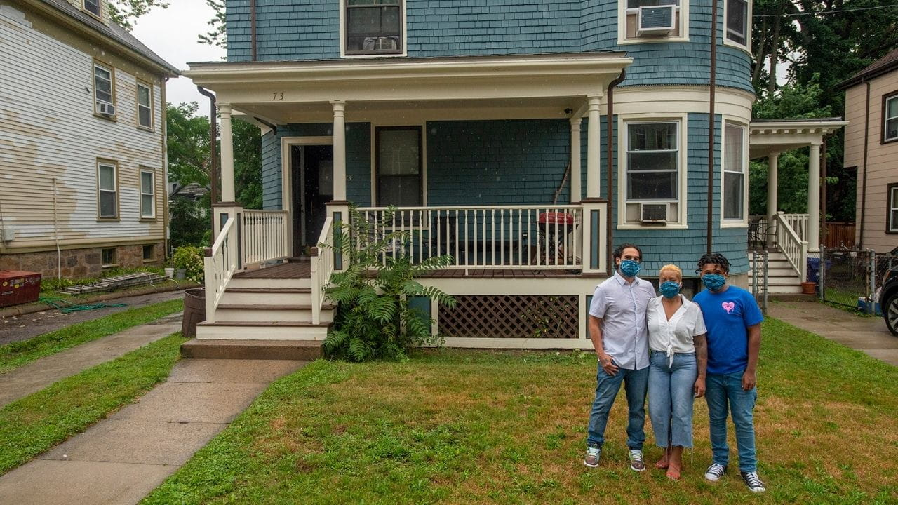 From left to right, Mike, Taheera and Christian Massey are standing in their yard, front of and to the right their teal house in Dorchester. Mike and Taheera are wearing white t-shirts and jeans, and Christian is wearing a blue t-shirt and jeans. The grass is green and brown in their yard. To the left is a paved walkway leading up to their brown and white front porch.