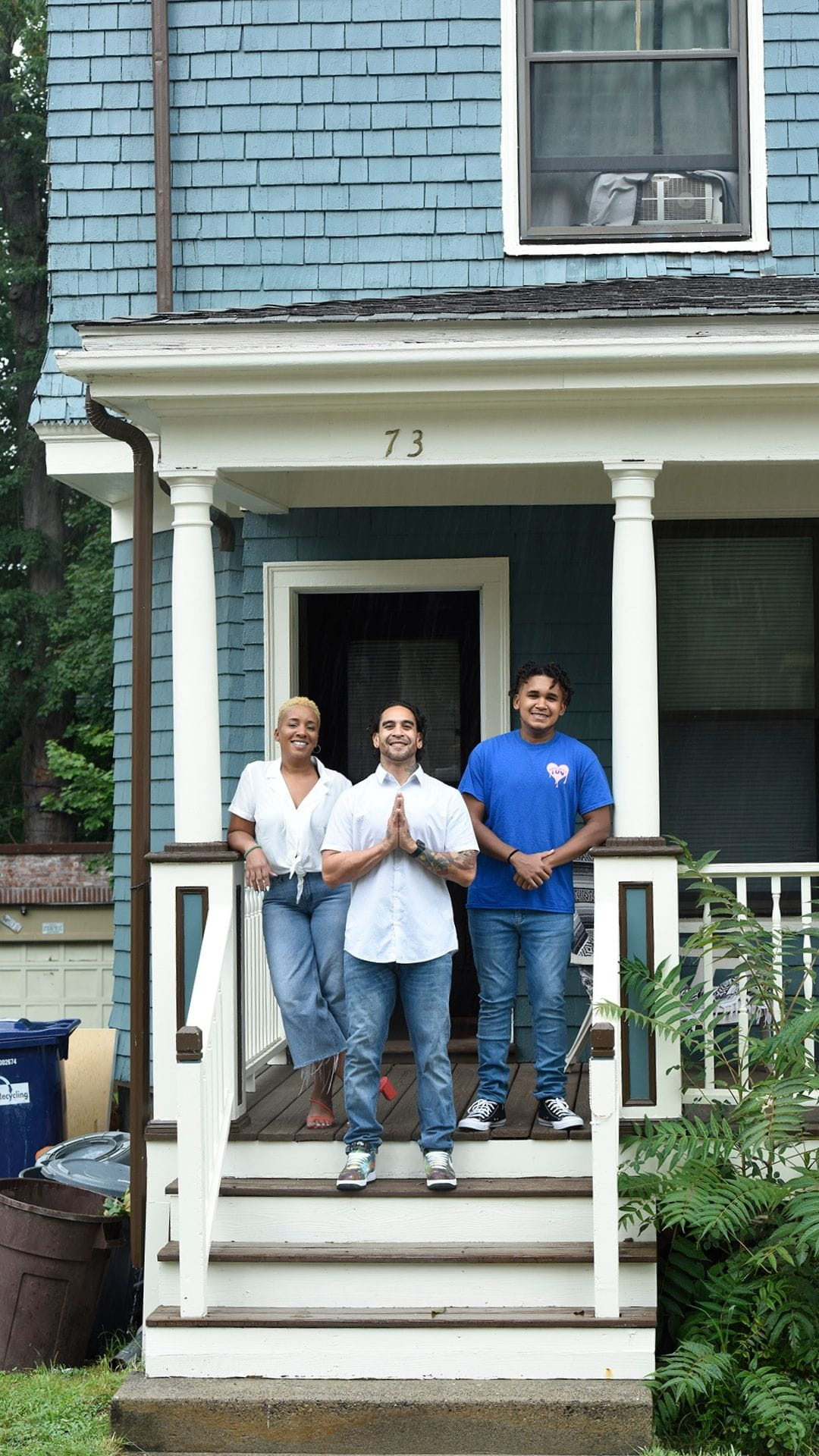 From left to right, Taheera, Mike and Christian Massey standing on the front porch steps of their teal house in Dorchester. The steps are brown and wooden with white molding. Taheera and Mike are wearing jeans a white t-shirts. Christian is wearing a blue T shirt. Green grass a leafy shrubs are in front of/to the right of the steps.
