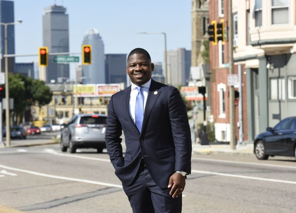 Rev. Willie Bodrick standing center frame on a meridian. In the background is a main road with cars on it, storefronts to the right, and the Prudential Center and One Dalton to the left. The sky is blue. Willie is wearing a dark blue suit, a light blue collared shirt and a blue tie. One hand is in his pocket.