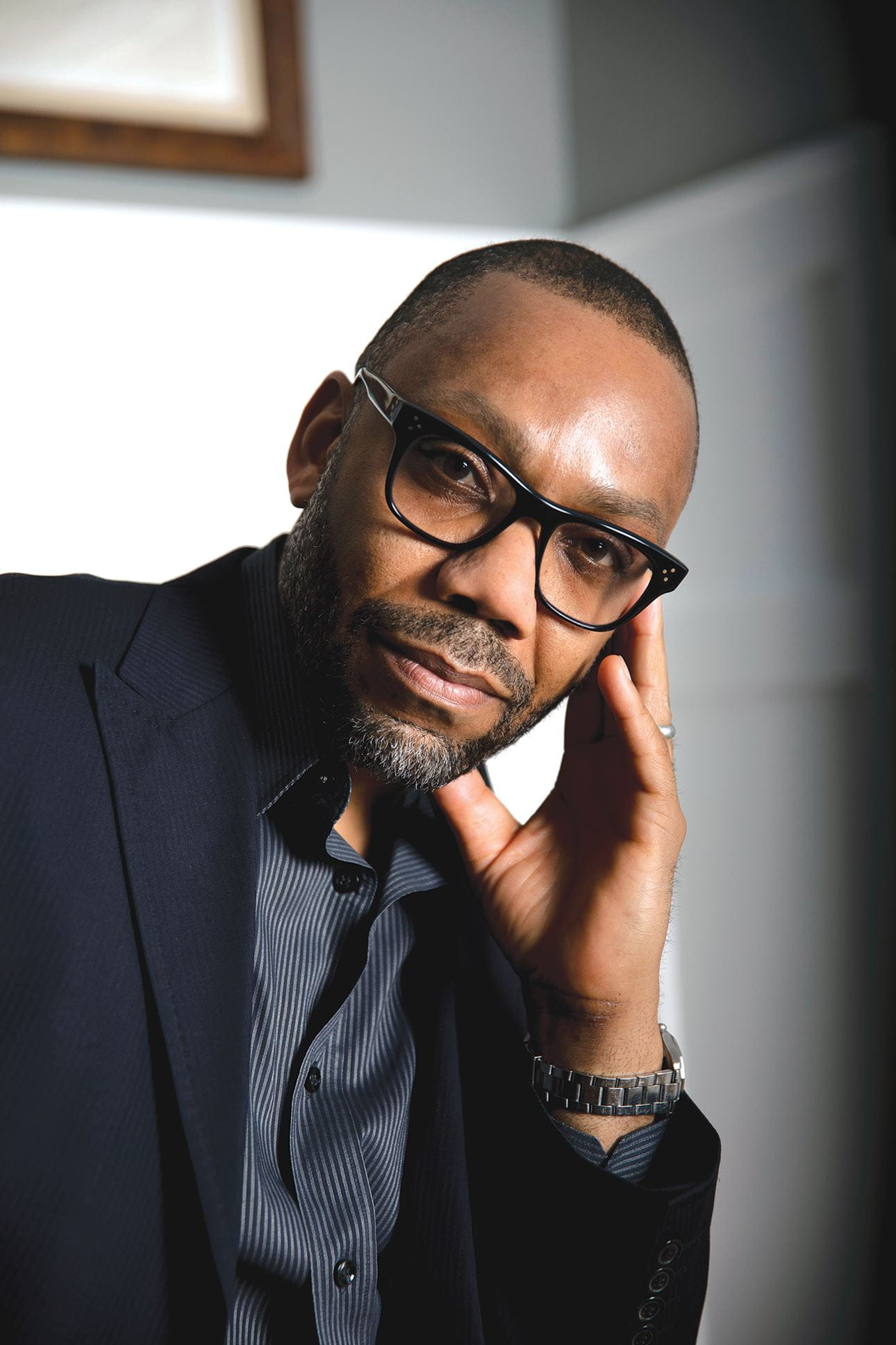 Headshot of Andre Perry. He's leaning his head on his hand, wearing a black blazer and black framed glasses.